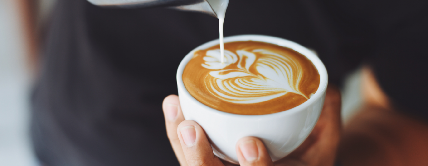White mug with latte art being poured